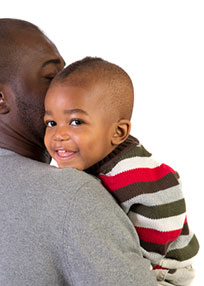 African American man holding smiling son