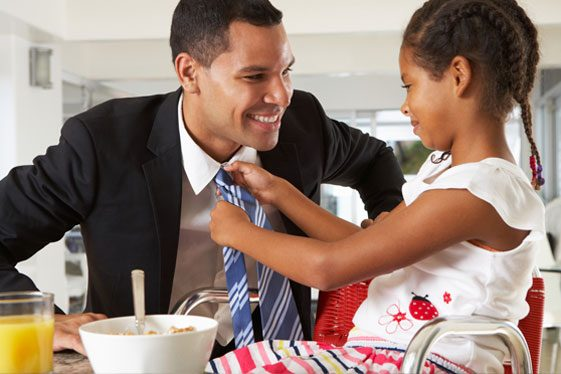 Father playing with daughter tying tie