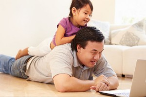 Father watching movie with daughter on laptop