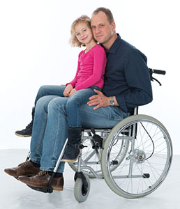 Man in wheelchair holding daughter in lap