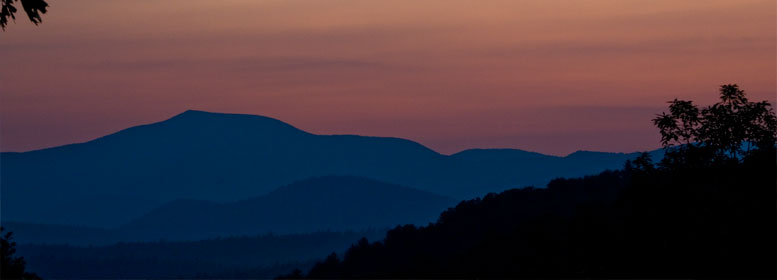 Sun setting behind mountains on horizon
